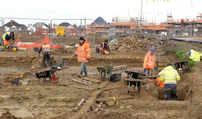 Archaeologists at work on the Roman bath house that has been uncovered on the Bovis site in Box Road, Cam.