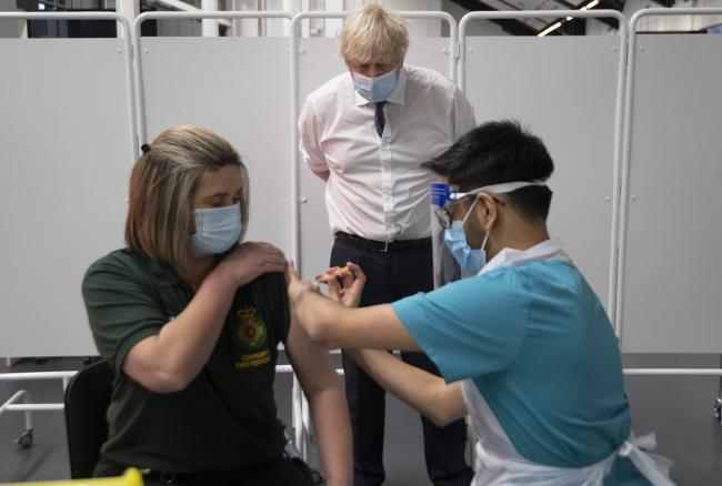 Prime Minister Boris Johnson at Ashton Gate Stadium in Bristol watches first responder Caroline Cook receiving an injection of a Covid-19 vaccine during a visit to one of the seven mass vaccination centres now opened to the general public as the governmen