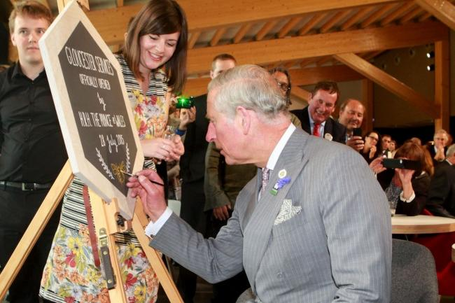 The Prince of Wales puts the finishing touches on a mural created by Steph Cole to mark the opening of Gloucester Services in 2015 // Carl Hewlett - Thousand Word Media