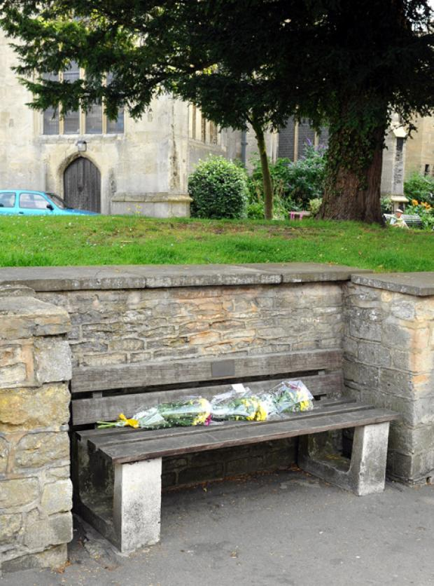 Flowers on the bench outside St James' Church where Alex Docherty was found.
