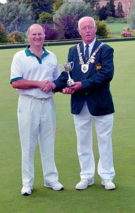 Keith Hinder being presented with the champion of champions trophy by Gloucestershire president Ian Deakin
