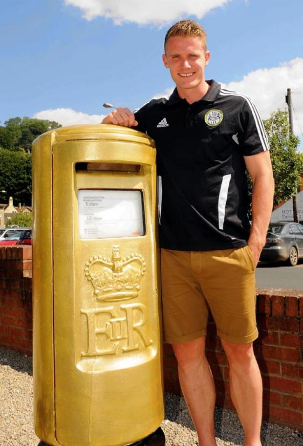 GOLD FEVER: Forest Green midfielder and former postman  Yan Klukowski next to Pete  Reed's golden Nailsworth postbox