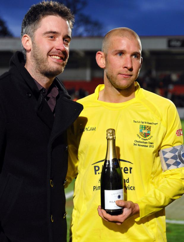 Edd Vahid is presented with his bottle of champagne by Simon Pick, director of match sponsors Picksons