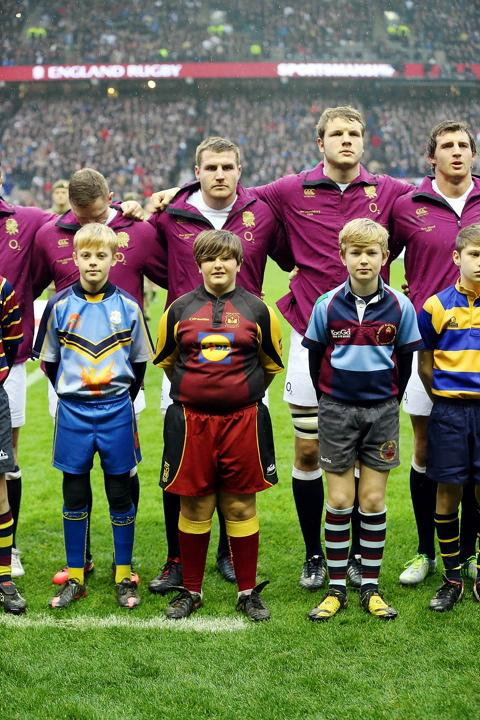 England's Ben Morgan (second in from left on back row) with mascot Esme Harper-Coles in her Dursley kit during the national anthem at Twickenham