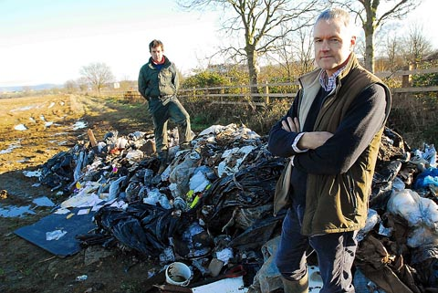 Tenant farmer, Dan Moss (left) and Cllr Haydn Jones with the huge amount of rubbish that has been dumped on fields near Wisloe Stables, Cambridge, near Slimbridge