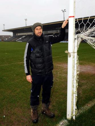 FGR groundsman Stewart Ward showing the amount of rain which fell on The New Lawn playing surface in 2012