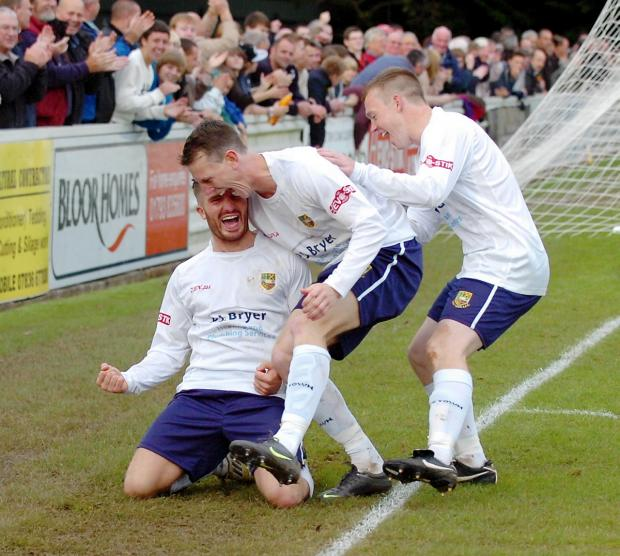 Tom Knighton (on his knees) celebrates scoring for Yate against Newport in the FA Cup last season