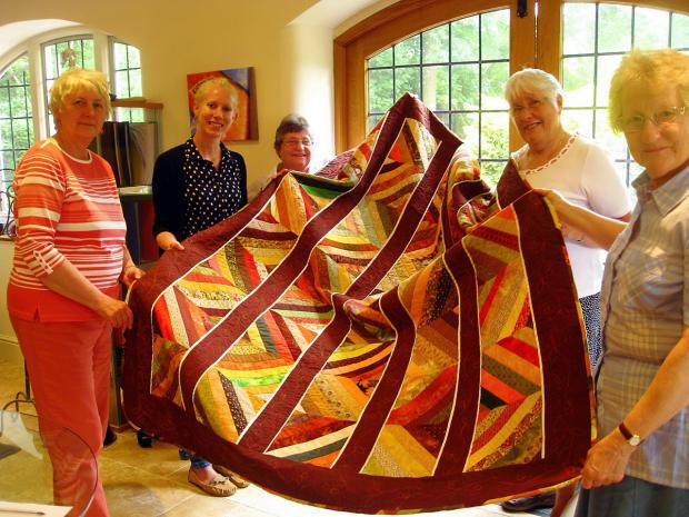 The quilt being presented to Rosa Woodley from Hope for Tomorrow (second from the left) by Pat Owen, Maisie Phillips, Wendy Naish and Ann Vick of Stinchcombe Quilters