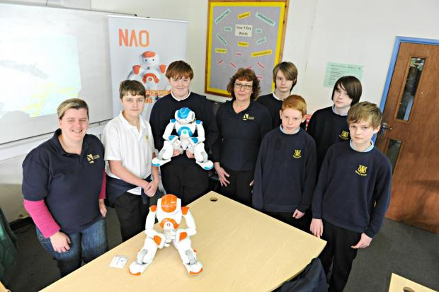 Nao robots Ben(orange) and Anthony(blue) with Castle School students James Macdonald,14, Chris Rowe,15, Sam Kemp,14, James Warnock,13, Tom Channelle,12, and Luke Scarbrough,12, and Charlie Newton and Joanne Dawe-Lane of Active Robots. The Robot workshop w