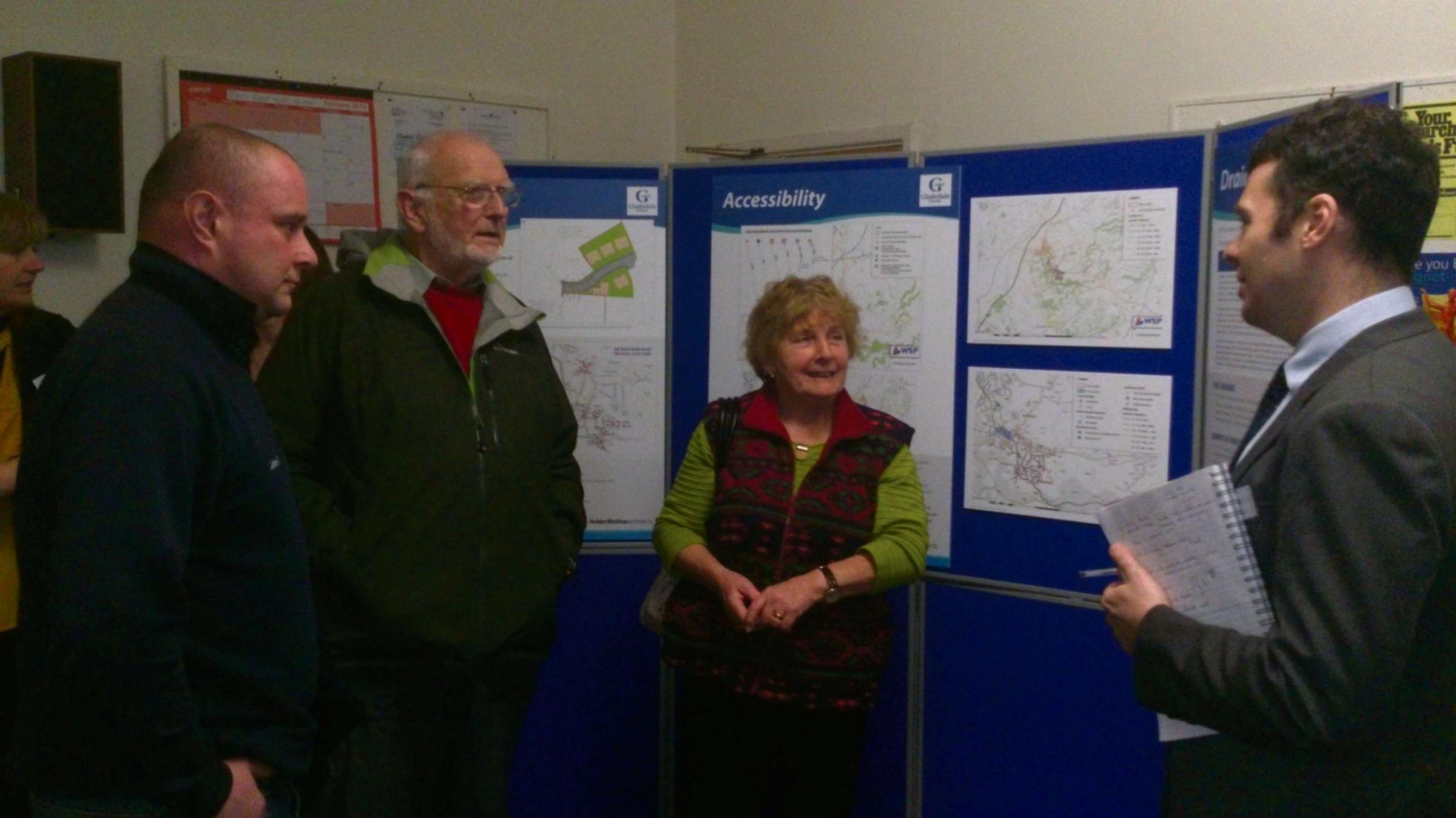 Residents talk to a Hunter Page Planning staff member about the plans for 100 homes in Woodmancote (4346435)