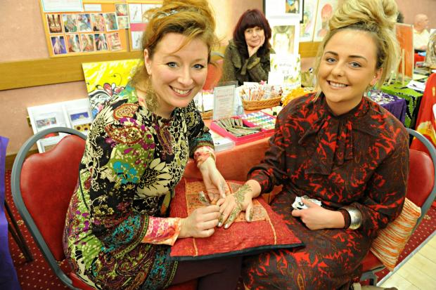 Nicola King of Henna Heaven painting the hand of Tanya Manasievska at the mind, body and spirit show at Chipping Sodbury Town Hall