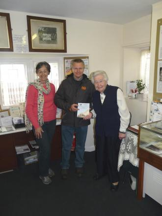 Frenchay Museum custodians Marylyn Phillips and Hazel Copsey, with 25,000th visitor Martyn Carr