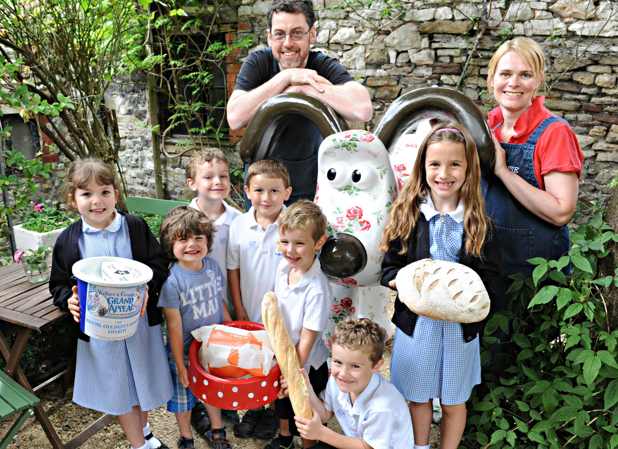 Andrew Houghton and Jo Cox of Hobbs House Bakery with some younger customers and Antique Rose gromit who will be on a diet of Hobbs House bread over the next couple of weeks in the garden of the bakery in Chipping Sodbury