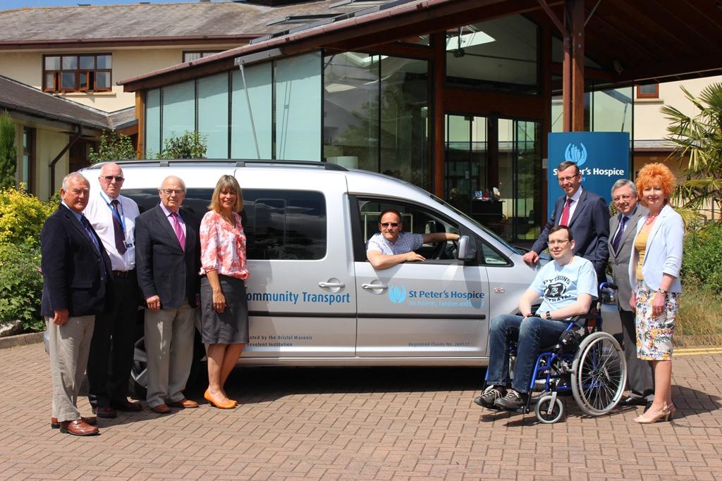 Marc Willetts, from the Bristol Masonic Benevolent Institute, with Simon Caraffi, chief executive of St Peter's Hospice (standing to the right of the bus) and members of the mason with patients and their families
