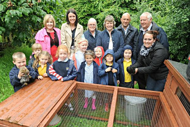 Reception class pupils of Olveston Primary School with staff, parents and sponsors with a couple of their chickens and their new chicken coop (6843461)