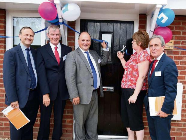 Resident Sue Organ cuts the ribbon at new affordable homes in Falfield, joined by, from left, Steve Webb MP, Councillor John O'Neill, Councillor Matthew Riddle and Nick Medhurst, chairman of Knightstone's board. (7907427)