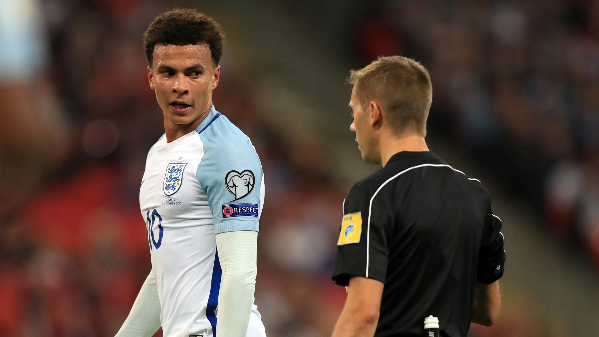 England midfielder Dele Alli speaks with referee Clement Turpin