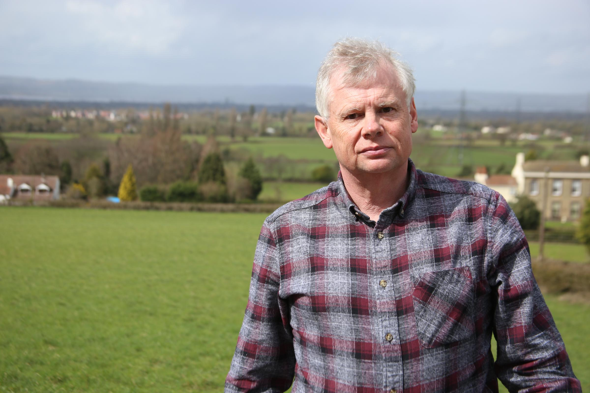 TRAPP'D co-chairman Colin Gardner in front of the proposed Buckover Garden Village site with Thornbury in the background