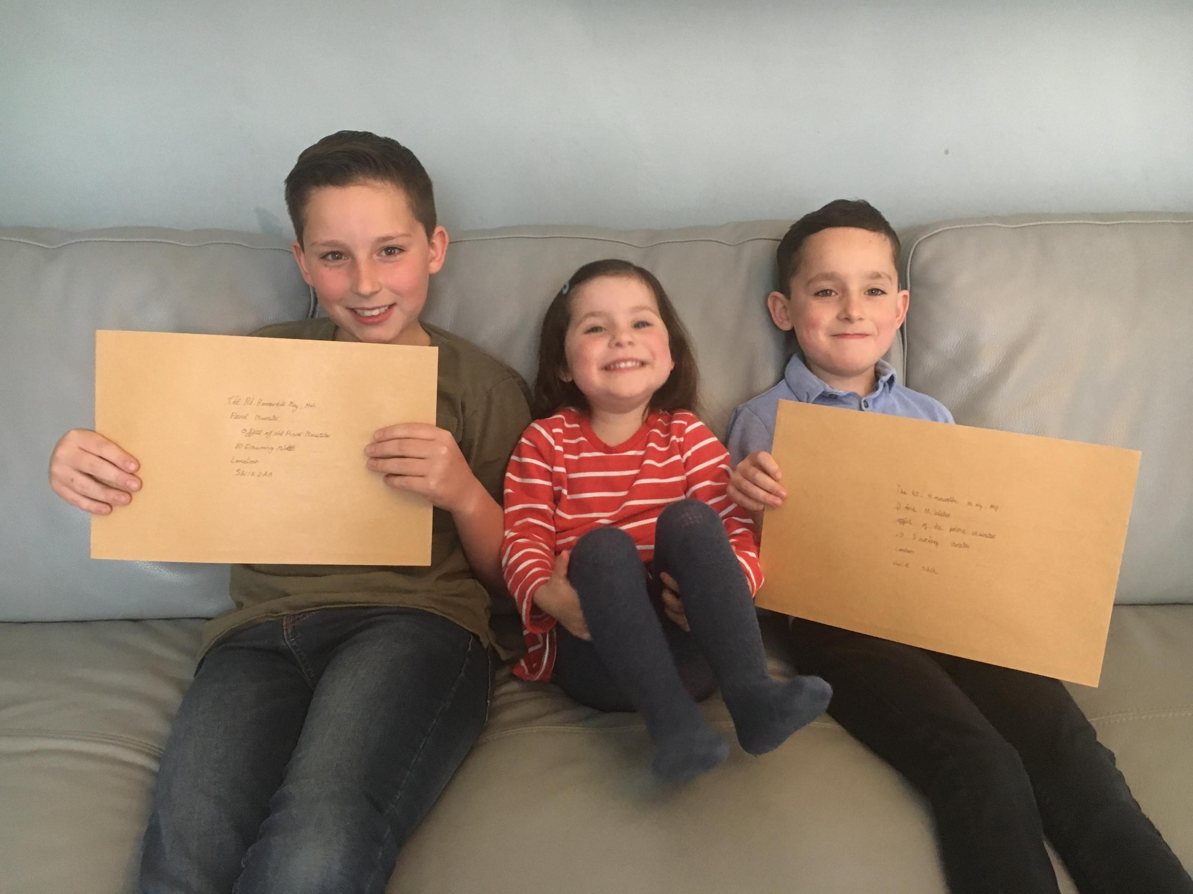 Brothers Finley, left, and Oscar Brennan holding their letters for Theresa May, inset, with sister Annabelle. Photo by Ross Arnott