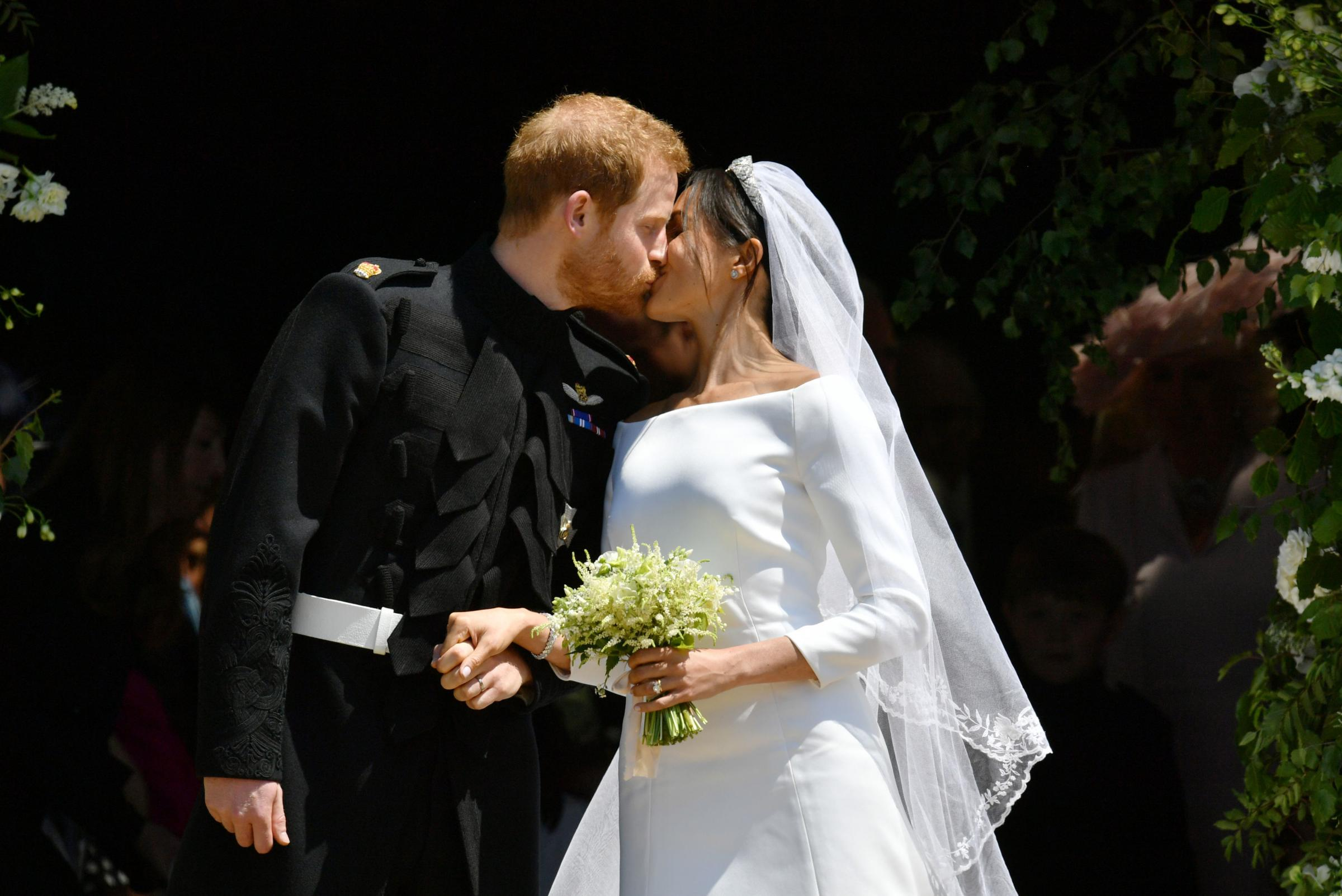 Prince Harry and Meghan Markle kiss as they leave St George's Chapel in Windsor Castle after their wedding Photo credit : Ben Birchall/PA Wire.