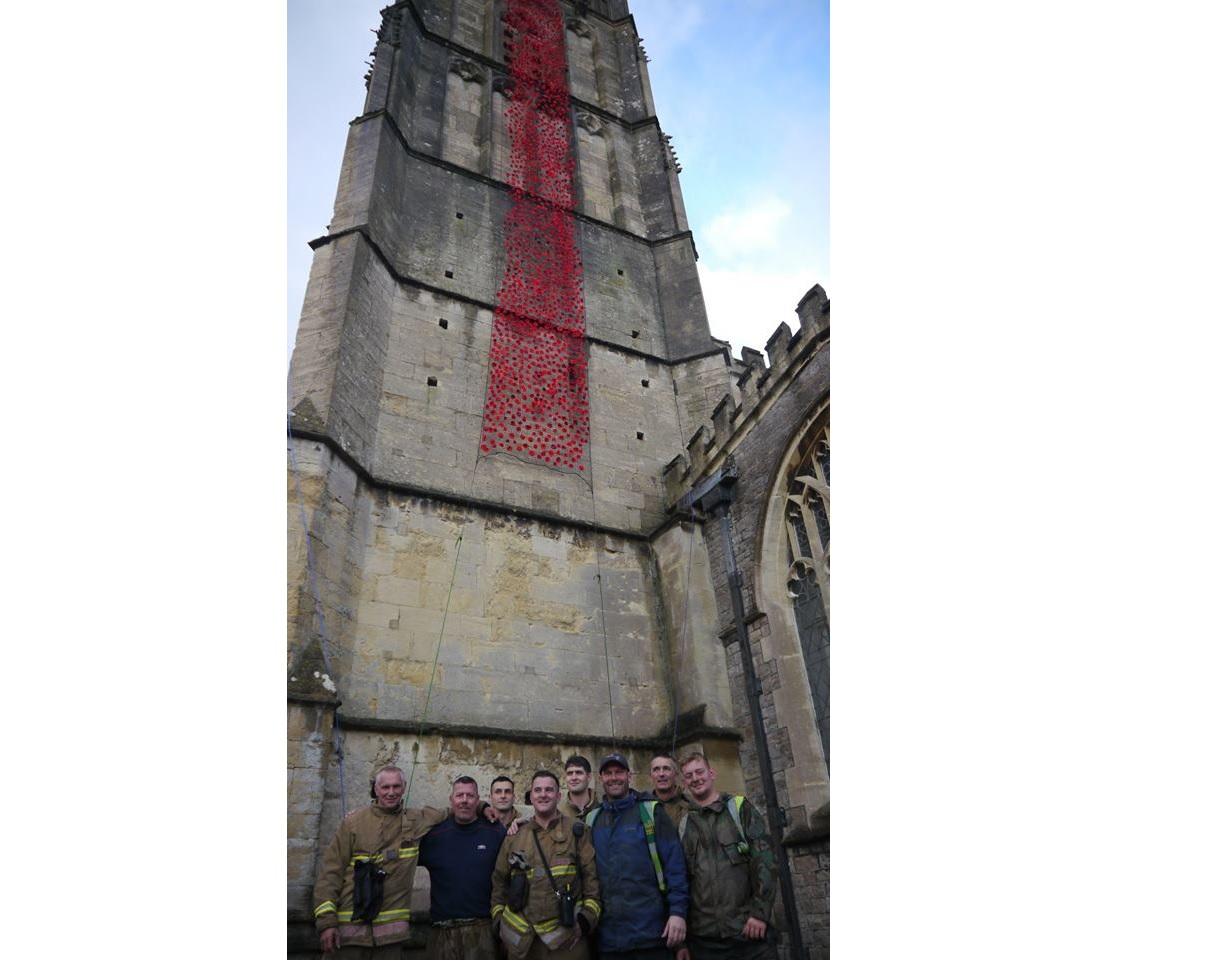 Fire crew help drape Wotton church tower in poppies
