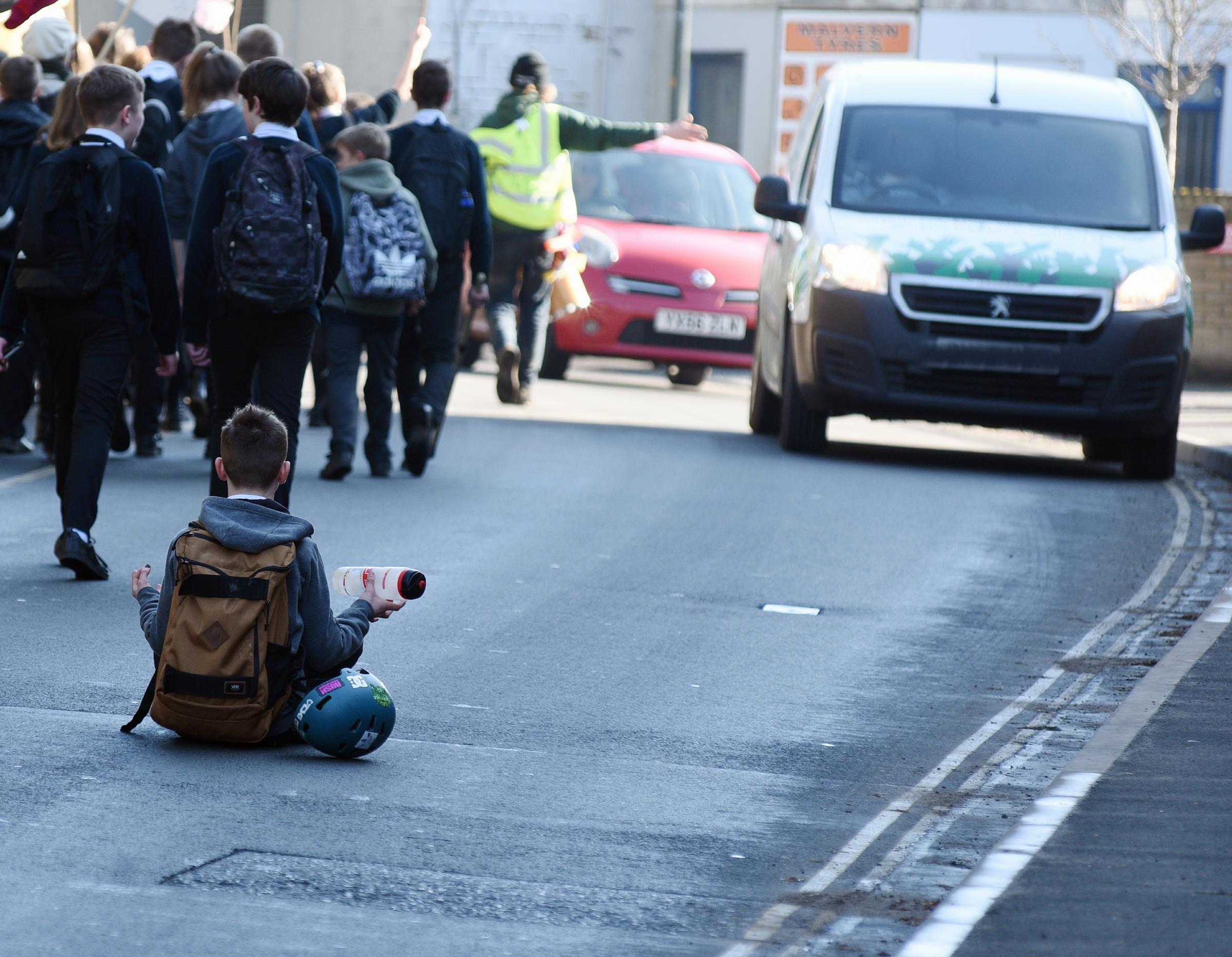 For a few fleeting moments this young boy sat in the road as traffic drove carefully past the protesters